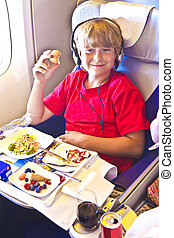 boy enjoys the dinner in the aircraft - boy enjoys the...