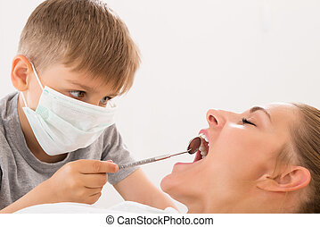 Boy Examining Teeth Of Woman