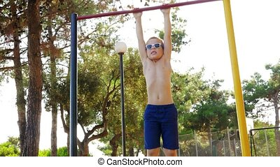 Boy exercising on chin-up bar at outdoor sports ground -...