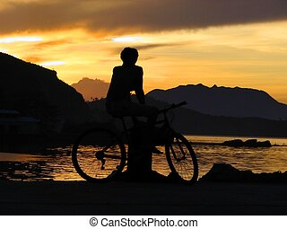 Boy exotic sunset - Boy on bicycle watching sunset in...