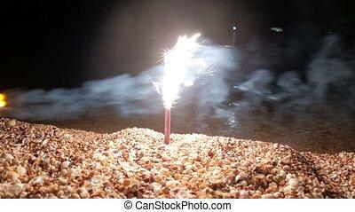 Boy fire sparklr in beach sand