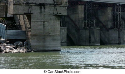 Boy fishes around hydroelectric