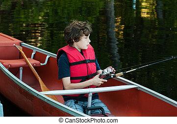 boy wearing a lifejacket fishing in a canoe