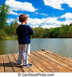 Boy fishing from dock on lake