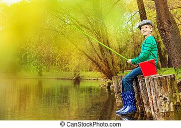 Boy fishing near beautiful pond with fishrod