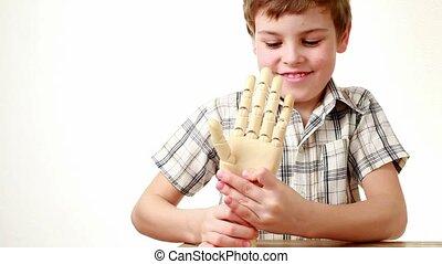 boy flexes wrist of wooden model of human hand