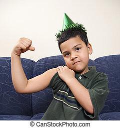 Boy flexing arm muscle. - Hispanic boy wearing party hat...