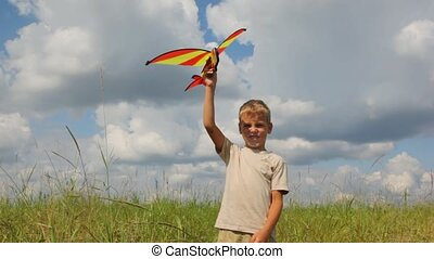 boy flying toy airplane in the field