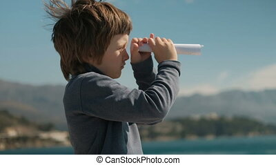 boy fold piece of paper looking into the distance trumpet to mountains
