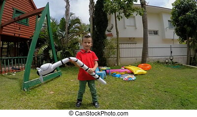 boy fooling around with inflatable toys