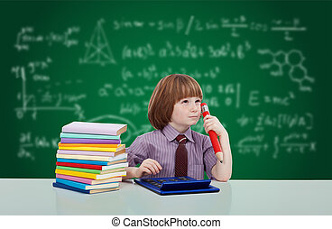 Boy genius - young child with books in front of blackboard...