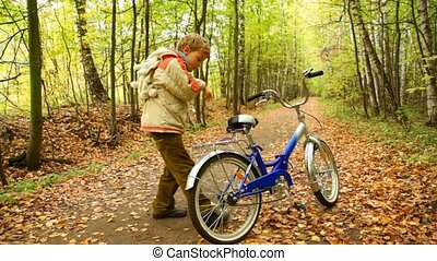 boy get on bicycle and riding in autumn forest with leaves