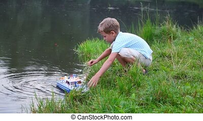 boy get toy ship from water