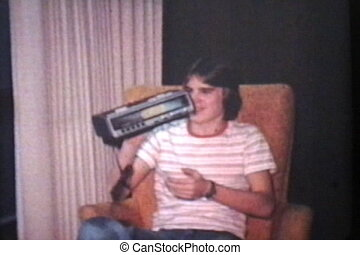 A cool retro looking teenage boy gets a funky clock radio for his birthday. (Scan from archival 8mm film)