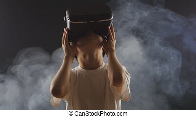 boy getting experience in using VR-headset in a smoky dark room