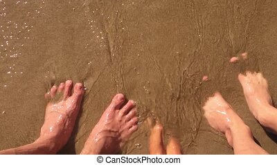 boy girl water and man family legs in the ocean slow motion video. strong waves of sand sea rest family