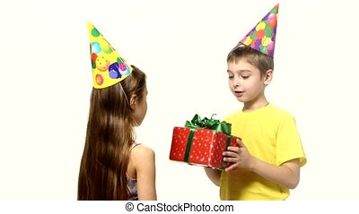 Boy gives a girl gift red. They are both in festive caps on white background
