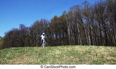 boy goes on bicycle across the field in spring