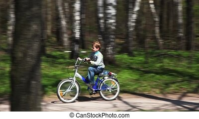 boy goes on bicycle on forest road in spring