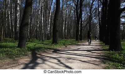 boy goes on bicycle towards to people on forest road in spring