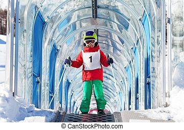 Boy going uphill under archway using ski lift