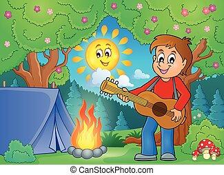 Boy guitar player in campsite