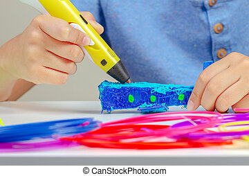 Boy hands creating with 3d printing pen new object
