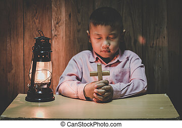 Boy hands holding a holy cross and praying to God,.