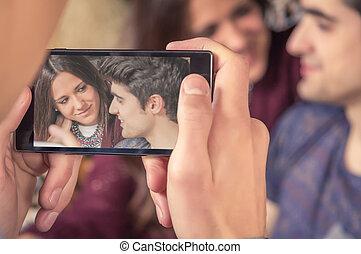Boy hands taking photos to teenage couple on sofa
