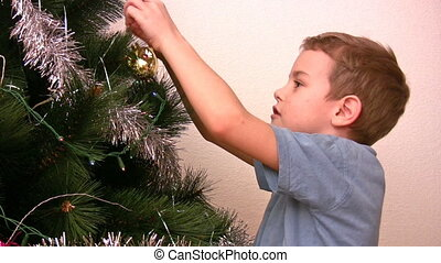 boy hangs up fur-tree toy on christmas tree