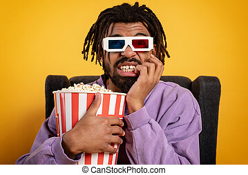 Boy has fun watching a film. Concept of entertainment and streaming tv. yellow background