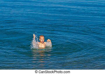 boy having fun and swimming in the sea