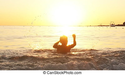 Boy having fun in sea at sunset, slow motion