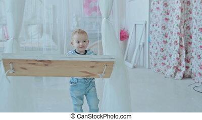 Boy having fun near white swing