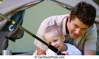 Boy having fun with his father by fishing