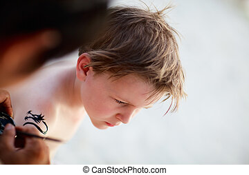 Boy having henna tattoo