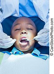 Boy having his teeth examined
