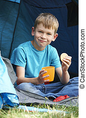 Boy Having Snack On Camping Trip