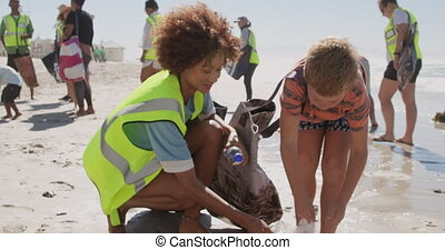 Front view of Caucasian boy helping female volunteer in cleaning beach. They are picking up trash 4k