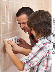 Boy helping his father install the front panel of electrical wall fixture
