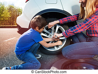 Boy helping mother to change tyre using lug wrench - ...