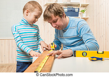 boy helps his father in the work of the carpenter