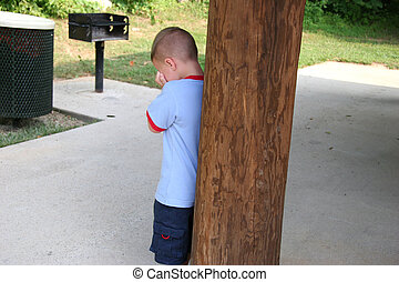 Boy Hiding Crying - Five year old boy crying behind pole at...