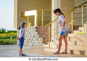 Boy Hiding Ice Cream While Being Scolded by Mother