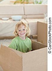 Boy hiding in cardboard box