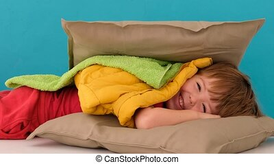 Little charming boy in bright pants lying on pillow covered with blanket towel and another pillow on blue backdrop