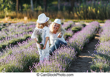 Boy hiding lavender behind his back. Little boy giving a bouquet of flowers to his mom. Motherhood Love Care Concept