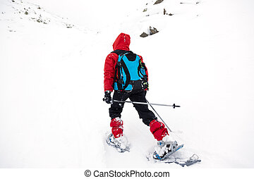 Boy hikes in mountain with snowshoe - A young boy is walking...