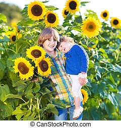 Boy his baby sister in sunflowers