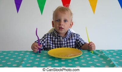 boy hit table with plastic knife and fork and waits for food. Gimbal motion